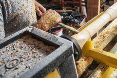 De arbeiderstimmerman verwerkt een hout op een draaibank stock foto