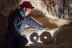 De archeoloog bekijkt het steenwiel door backlight in de holen wordt verlicht dat stock foto