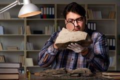 De archeoloog die laat - nacht in bureau werken stock afbeeldingen