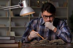 De archeoloog die laat - nacht in bureau werken stock fotografie