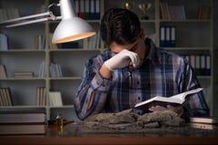 De archeoloog die laat - nacht in bureau werken royalty-vrije stock foto's