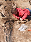 De archeoloog graaft zorgvuldig menselijke beenderen op stock afbeelding