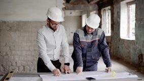 De architect en de bouwingenieur bespreken plan en blauwdruk op de lijst Twee mensen in bouwvakkers bevinden zich  stock video