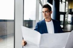 De architect in modieuze kleren houdt blad met tekening in zijn hand en spreekt telefonisch op de achtergrond van een modern glas stock afbeelding