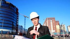 De architect op de plaats leest de documenten stock video