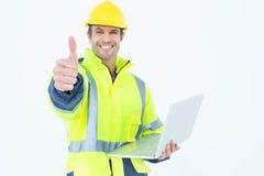De architect in weerspiegelende kleding met laptop het gesturing beduimelt omhoog Stock Foto's