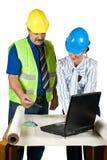 De architecten in bureau raadplegen en kijken op projecten Stock Afbeeldingen