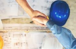 De architecten, de ingenieurs en de zakenlieden sluiten zich aan bij handen voor eenheid stock afbeeldingen