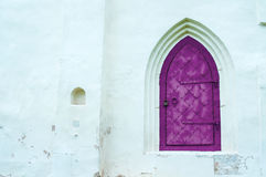 De architectuurmening van architectuurelementen verouderde donkere magenta metaal gesmede deur met arcade op de witte steenmuur Stock Foto's