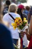 De arm en de hand van het zwarte aangezien zij een boquet van bloemen met stammen houdt in plastiek als vage onherkenbare menigte stock foto's