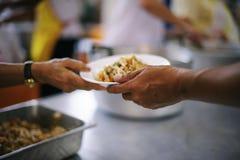 De armen hebben voedsel van de vriendelijkere maatschappij gedeeld om Honger te verlichten: Het Concept het Voeden stock fotografie