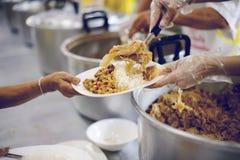 De armen ontvangen geschonken voedsel van donors, aantonen het wederzijdse delen in de maatschappij van vandaag: het concept het  royalty-vrije stock foto