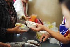 De armoede in de maatschappijarmen heeft voedsel van de filantroop geschonken: Conceptenarmoede en schenking: De vrijwilligers de royalty-vrije stock foto