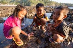 De armoedekinderen spelen op het strand in Indonesië stock afbeelding