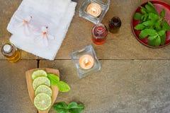 De aromatische olie, gebrande kaars, roze bloemen, sneed kalk, groen blad, witte handdoek op de uitstekende achtergrond van de gr Stock Afbeelding