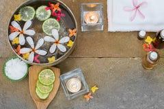 De aromatische olie, gebrande kaars, roze geeloranje bloemen, sneed kalk, witte handdoek op de uitstekende achtergrond van de gru Royalty-vrije Stock Afbeelding
