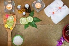 De aromatische olie, gebrande kaars, roze gele, oranje bloemen, groene bladeren, sneed kalk, witte handdoek op uitstekende grunge Royalty-vrije Stock Afbeelding