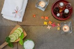 De aromatische olie in houten kom, gebrande kaars, roze geeloranje bloemen, sneed kalk, blad, witte handdoek op steenachtergrond Royalty-vrije Stock Foto's