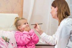 De arts bekijkt het de keelmeisje van de patiënt, stock afbeeldingen