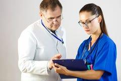 De arts bekijkt de resultaten van de verslagen van de verpleegster in de kaart, terwijl in het ziekenhuis stock foto's