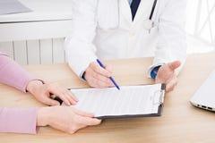 De arts bespreekt met vrouwelijk geduldig medisch contract bij de kliniek, medische verzekering royalty-vrije stock foto's