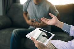 De arts bezocht de patiënt terwijl het gebruiken van tablet thuis verklarend over de geduldige maagpijn in de woonkamer royalty-vrije stock afbeeldingen