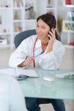 De arts bij telefoon het roepen analyseert centrum met patiënt royalty-vrije stock foto