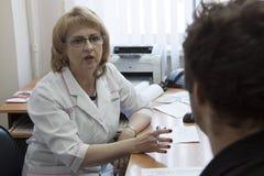 De arts communiceert met de patiënt stock foto's