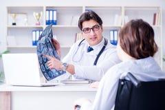De arts die aan geduldige resultaten van x-ray weergave verklaren stock afbeeldingen