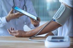 De arts die bloeddruk van oudere patiënt via tablet controleert dient het ziekenhuis in royalty-vrije stock foto