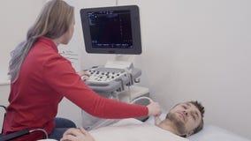 De arts die monitor bekijken en controleert de kenmerkende ultrasone klankschildklier stock footage