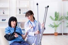 De arts die oude rijpe vrouw na incident onderzoeken stock afbeeldingen