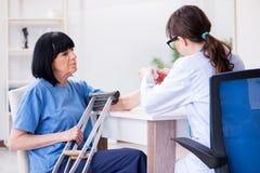 De arts die oude rijpe vrouw na incident onderzoeken stock foto