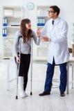 De arts die patiënt met gebroken been onderzoeken stock fotografie