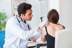 De arts die patiëntenoor controleren tijdens algemeen medisch onderzoek stock foto