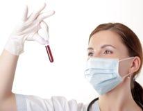 De arts die van de vrouw een bloedsteekproef bekijkt royalty-vrije stock afbeelding