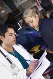 De arts die van het ziekenhuis nota'sparamedici neemt stock fotografie