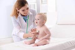 De arts die van kinderen baby met stethoscoop onderzoeken royalty-vrije stock afbeeldingen