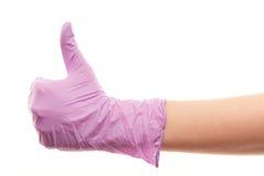 De arts dient purpere chirurgische handschoen in die de duimen omhoog ondertekenen tonen Stock Afbeeldingen