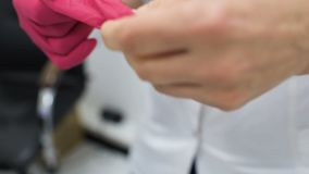 De arts draagt rode rubber medische handschoenen vóór chirurgie of vóór onderzoek van de patiënt stock videobeelden