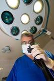 De arts in een blauw robe en een masker bekijkt het apparaat stock afbeeldingen