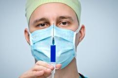 De arts in een groen GLB en een masker die een spuit met geneeskunde houden Royalty-vrije Stock Fotografie
