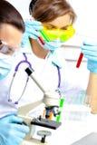 De arts in een masker onderzoekt reageerbuizen stock afbeelding