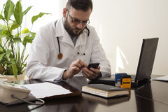De arts in een medische bureauzitting bij een bureau met een celtelefoon in zijn hand stock foto