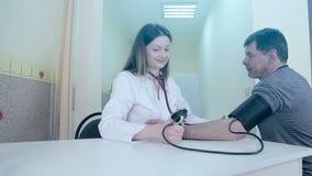 De arts is een vrouw die druk op een patiënt in een medische ruimte meet stock footage