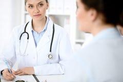 De arts en de patiënt communiceren terwijl het zitten bij de lijst royalty-vrije stock foto