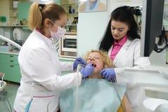De arts en de verpleegster bereiden vrouwelijke patiënt voor tandprocedure voor Stock Foto's