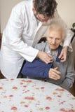 De arts en de verpleegster helpen de oude vrouw van de stoel opstaan Een oude vrouw met dient een slinger in stock foto