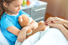 De arts en weinig patiënt met teddybeerholding dienen het ziekenhuis in royalty-vrije stock fotografie