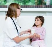 De arts geeft aan drank aan het zieke kind Stock Foto's